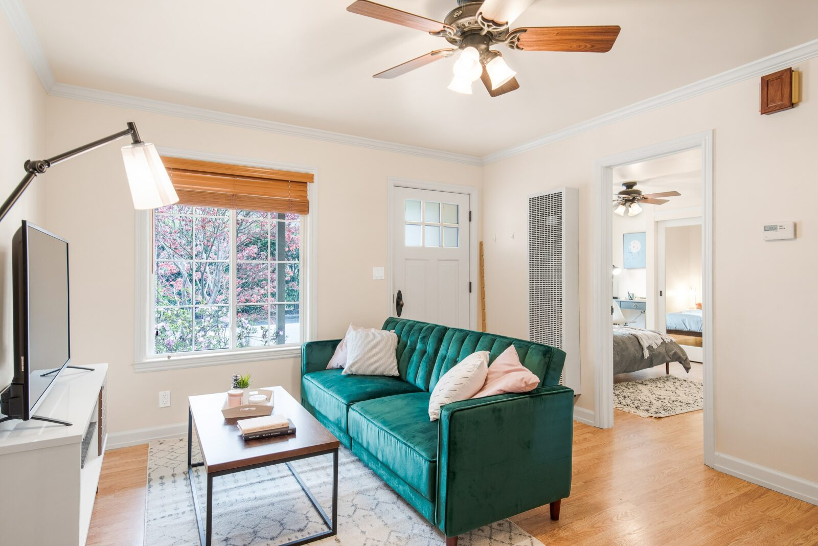 living room with a green couch and fan on the ceiling
